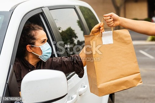 Caucasian mature woman picking her to go order from her car at a Curbside pickup