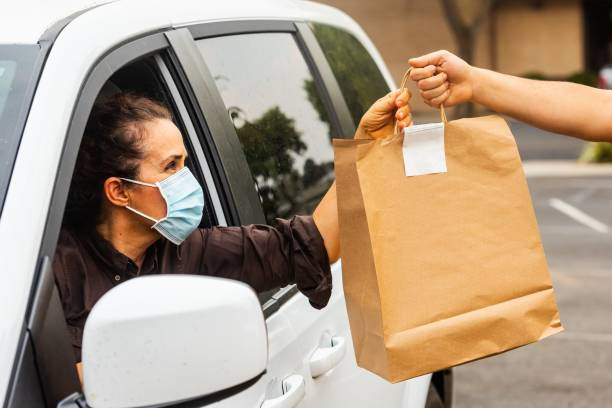 Mature woman picking her to go order from her car at a Curbside pickup Caucasian mature woman picking her to go order from her car at a Curbside pickup curbsidepickup stock pictures, royalty-free photos & images