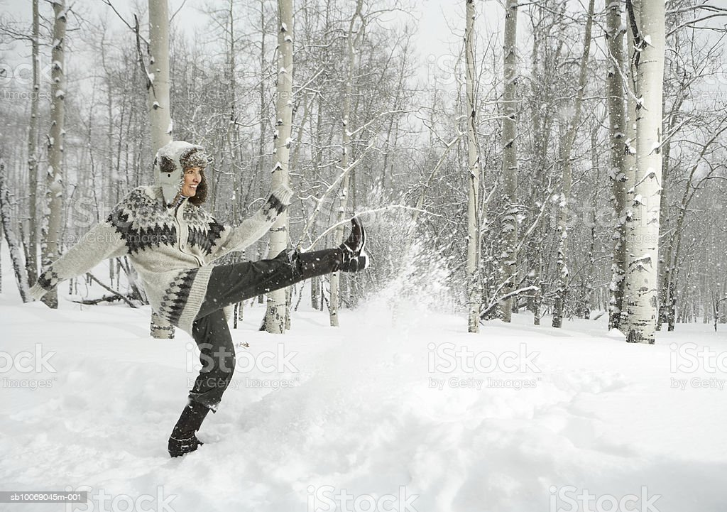 Mature woman playing in snow, smiling royalty free stockfoto