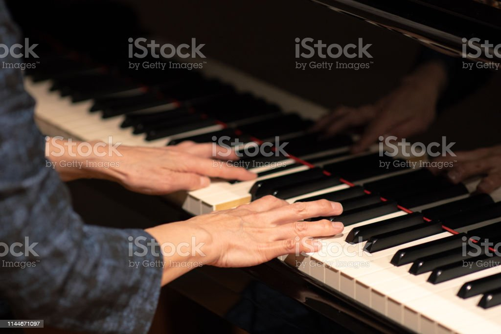 Mature woman playing piano at classical music concert