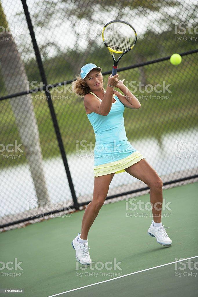 mature woman playing tennis stock photo