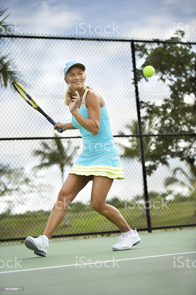 Mature woman playing tennis royalty-free stock photo