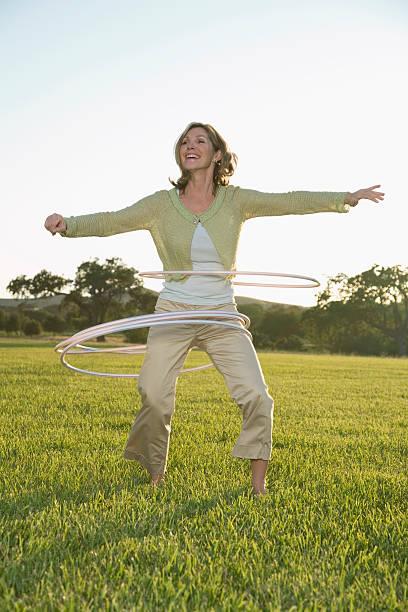 reife frau spielen mit hula-körbe auf gras - hula hoop workout stock-fotos und bilder