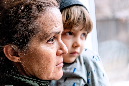 Caucasian Mature woman posing with her son, very sad looking through window worried about loss of her job due Covid-19 pandemic