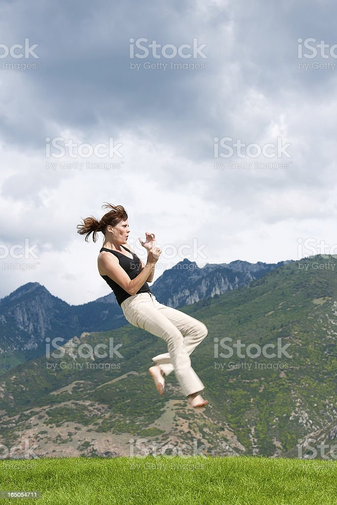 Mature woman practicing karate in scenic mountain area stock photo