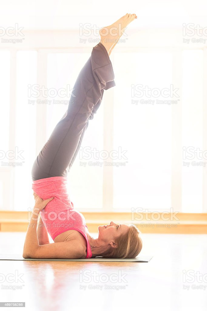 Mature woman practicing shoulder stand at home stock photo
