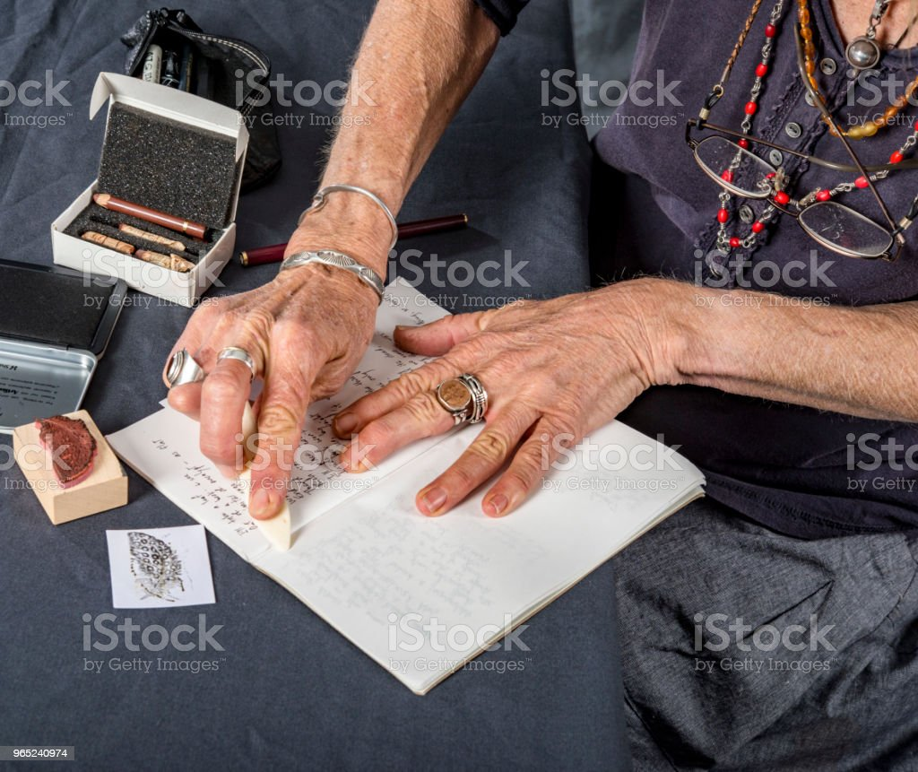 Mature woman prepares her notebook for writing and drawing. zbiór zdjęć royalty-free