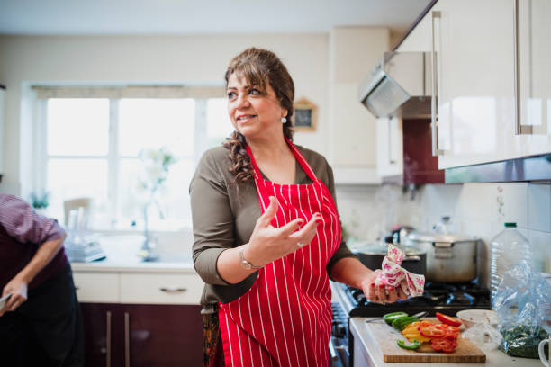 Mature Woman Preparing Food for Dinner Party stock photo