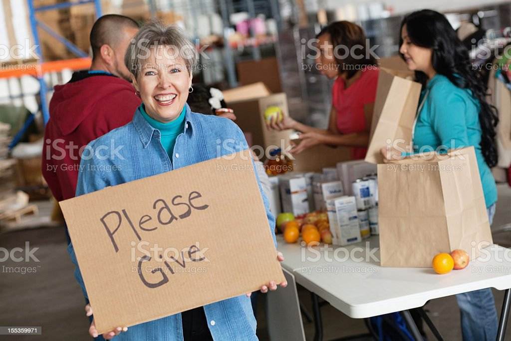 Mature woman promoting giving with a sign at donation center royalty-free stock photo
