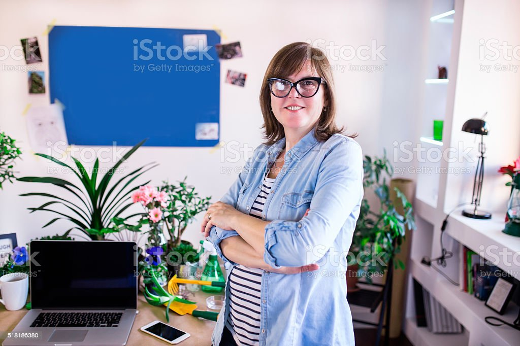 Mature woman proudly standing in her office and smiling stock photo