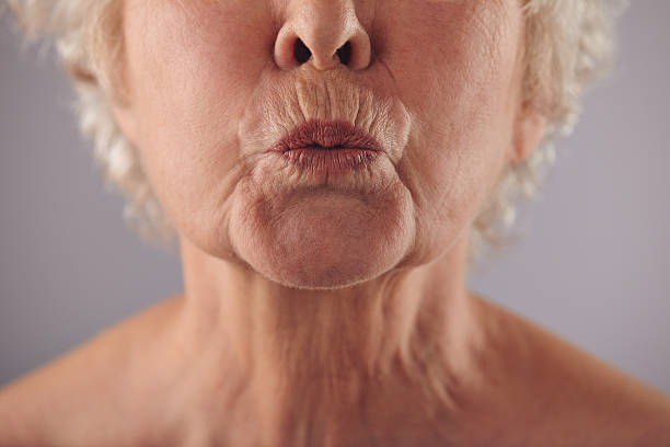 Mature woman puckering lips Close-up portrait of mature woman puckering lips against grey background. Senior woman grimacing. Focus on lips. using mouth stock pictures, royalty-free photos & images