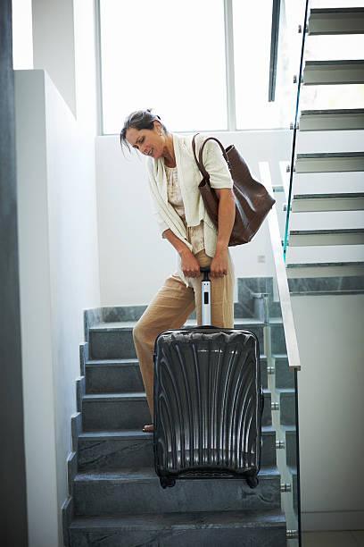 donna matura tirando la sua i bagagli pesanti fino alle scale - donna valigia solitudine foto e immagini stock