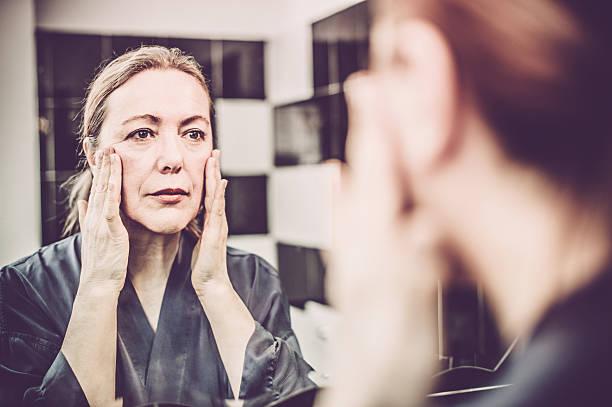 reife frau, die creme auf ihr gesicht setzen - alte spiegel stock-fotos und bilder