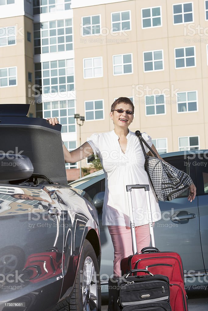Mature woman putting luggage in car royalty-free stock photo