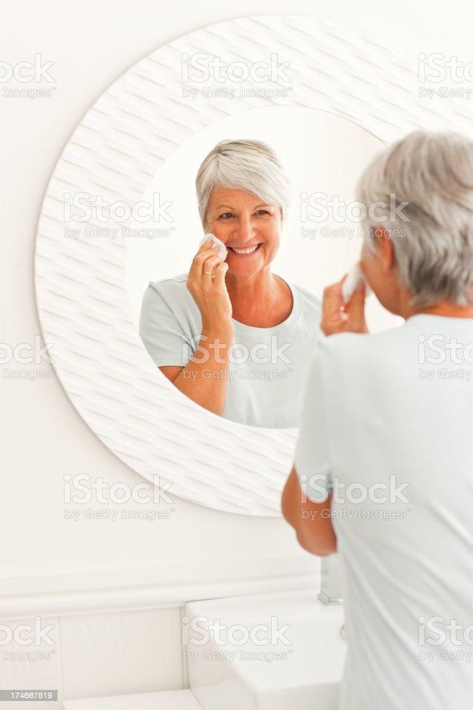 Mature woman putting on makeup royalty-free stock photo