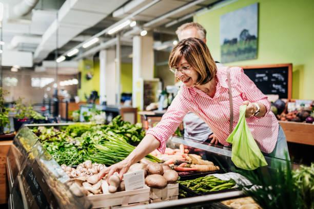 Reife Frau Erreichen für einige Pilze beim Lebensmittel-Shopping – Foto