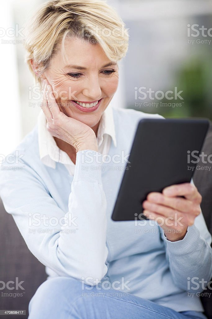 mature woman reading a book on tablet computer royalty-free stock photo