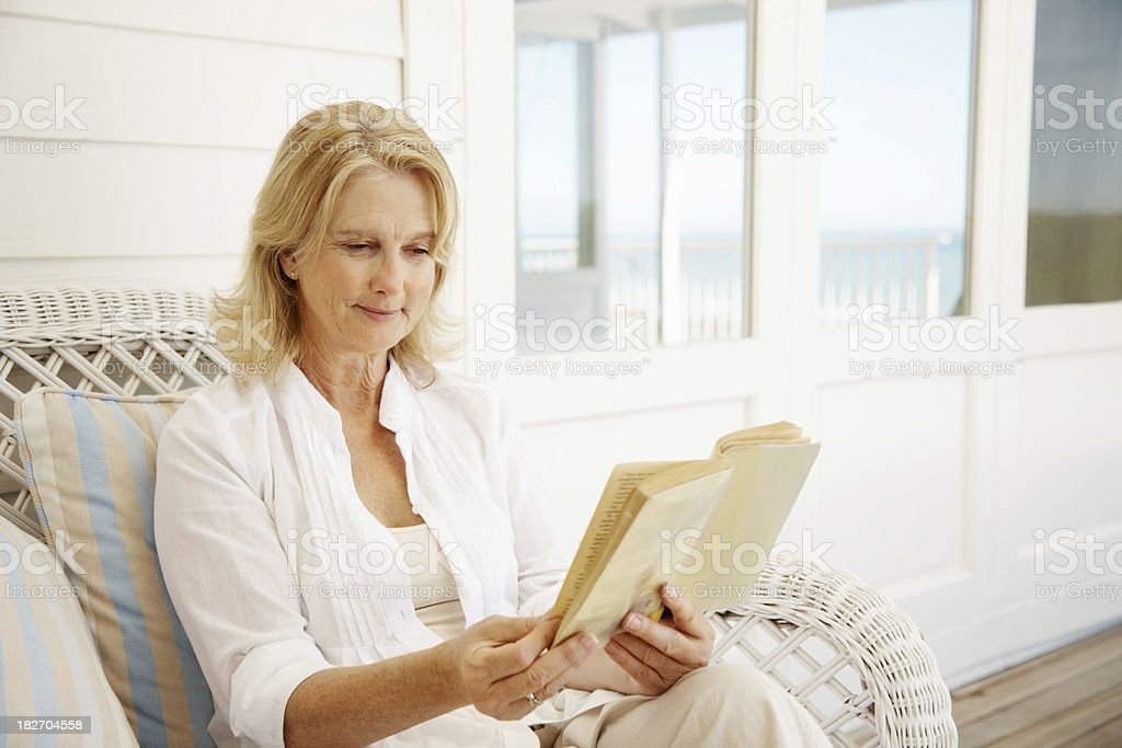 Mature woman reading a novel while at the porch royalty-free stock photo