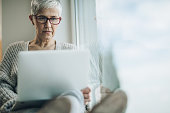 Senior woman sitting by the window and using computer. Copy space.