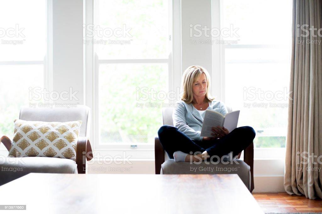 Reife Frau Buch auf Stuhl zu Hause – Foto