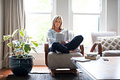 Full length of mature woman reading book on chair. Beautiful female is relaxing by houseplant against window. She is wearing casuals at home.