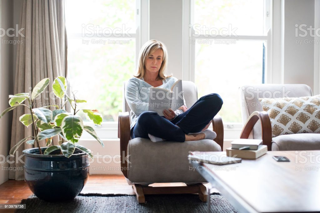 Mature woman reading book on chair at home stock photo