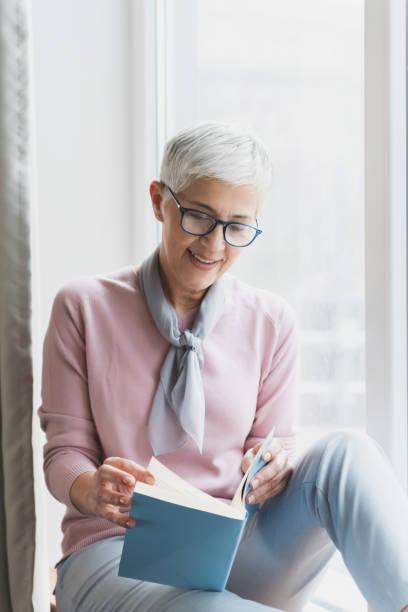 Mature woman reading book stock photo