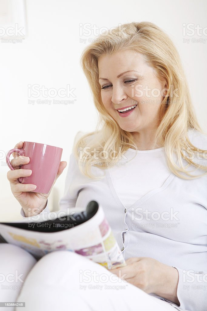 Mature woman reading magazine at home. royalty-free stock photo