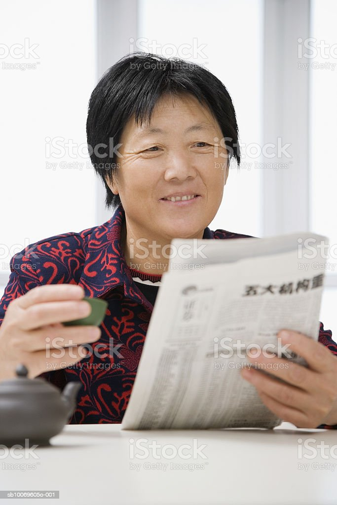 Mature woman reading newspaper and drinking tea, smiling foto de stock libre de derechos