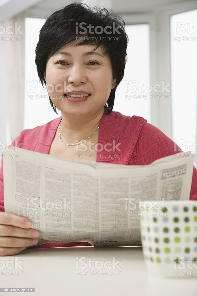 Mature woman reading newspaper, smiling, portrait royalty free stockfoto