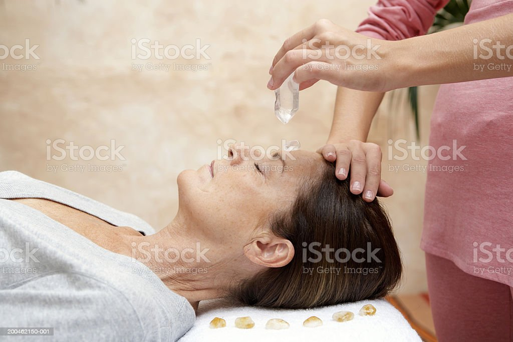 Mature woman receiving crystal healing treatment, eyes closed stock photo
