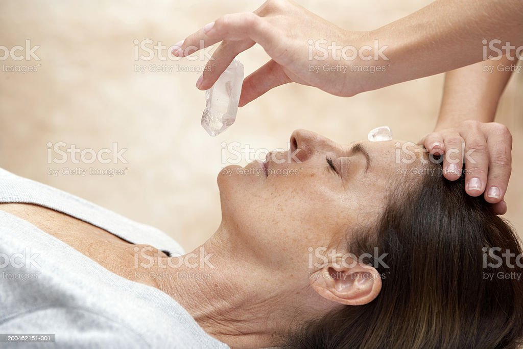 Mature woman receiving crystal healing treatment, eyes closed,close-up stock photo