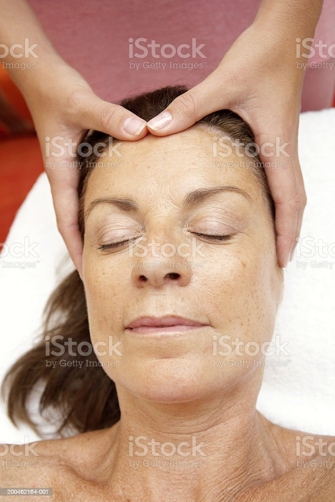 Mature woman receiving head massage, eyes closed, close-up royalty-free stock photo