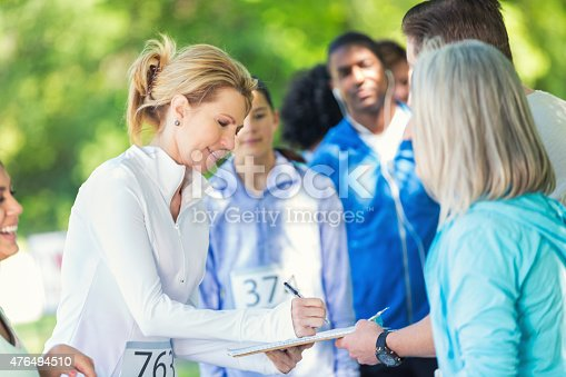 istock Mature woman registering to compete in marathon or 5k race 476494510