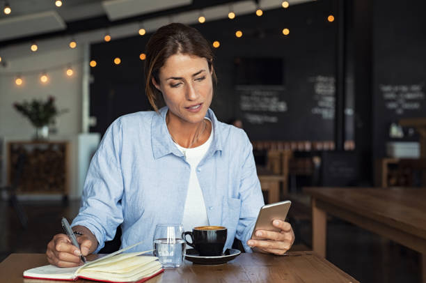 mature woman relaxing at cafe - older woman phone stock photos and pictures
