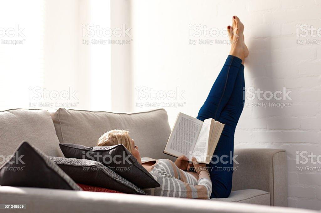 Reife Frau entspannend auf Couch bei der Lektüre eines Romans – Foto