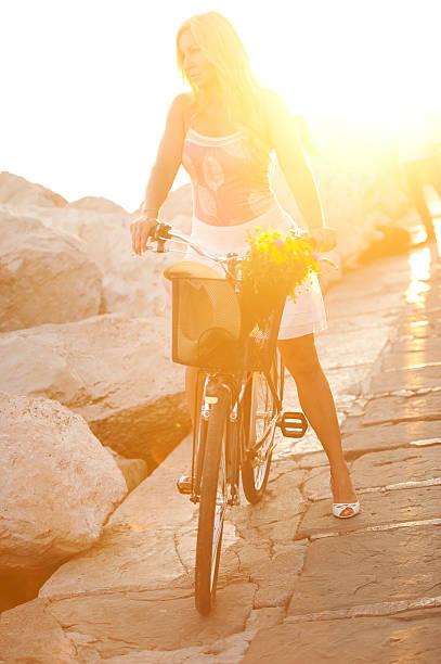 reife frau reiten fahrrad gegen sonne - damen rock pink stock-fotos und bilder