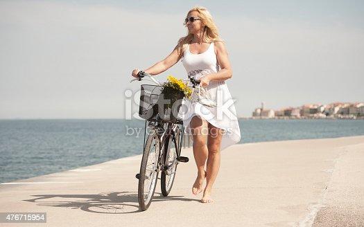 Mature woman riding bicycle against sun. Piran, Slovenia.