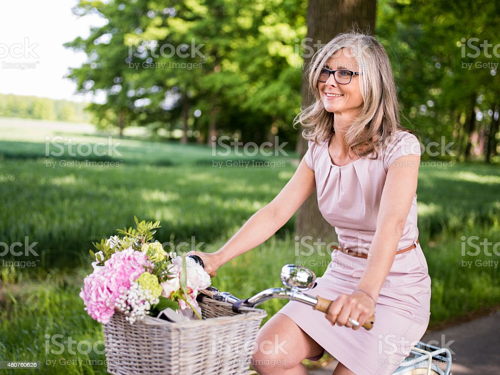 mature woman riding vintage bicycle through a summer park stock