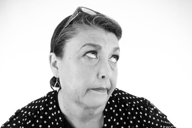 Mature woman rolling her eyes Humorous black and white head and shoulders shot of mature woman in polka dot top rolling her eyes. rolling eyes stock pictures, royalty-free photos & images