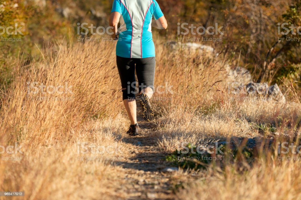 Mature woman running on the,grassy path at sunset,Italy,Europe royalty-free stock photo