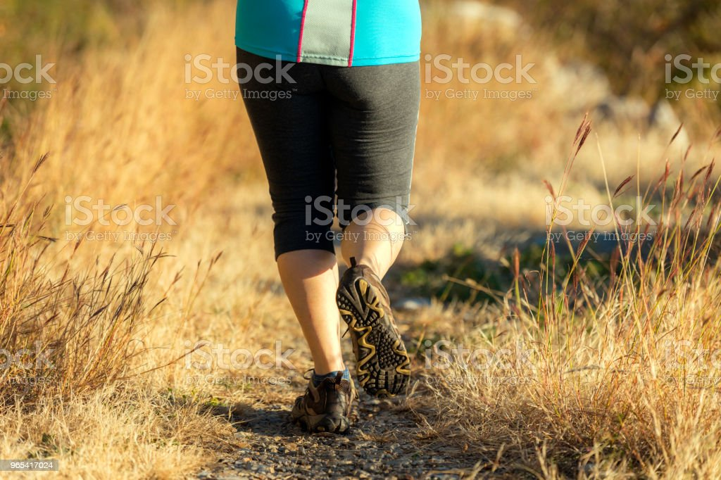 Mature woman running on the,grassy path at sunset,Italy,Europe zbiór zdjęć royalty-free