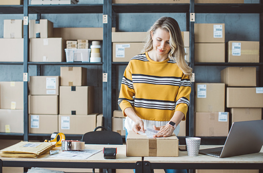 Mature woman at online shop. She is owner of small online shop. Receiving orders and packing boxes for delivery.