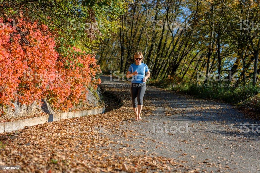 Mature woman running,barefoot runner,leaves, autumn, Slovenia, Europe zbiór zdjęć royalty-free
