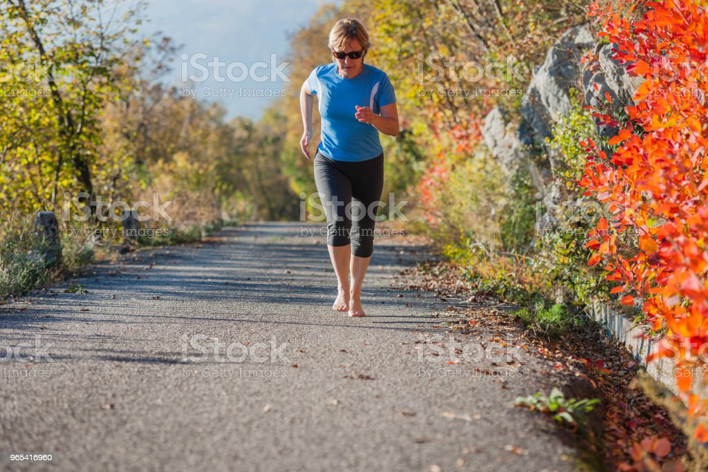 Mature woman running,barefoot runner,leaves, autumn, Slovenia, Europe zbiór zdjęć royalty-free
