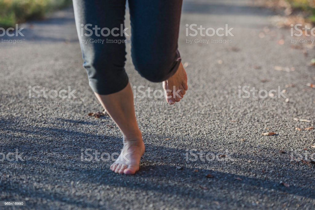 Mature woman running,barefoot runner,leaves, autumn, Slovenia, Europe royalty-free stock photo