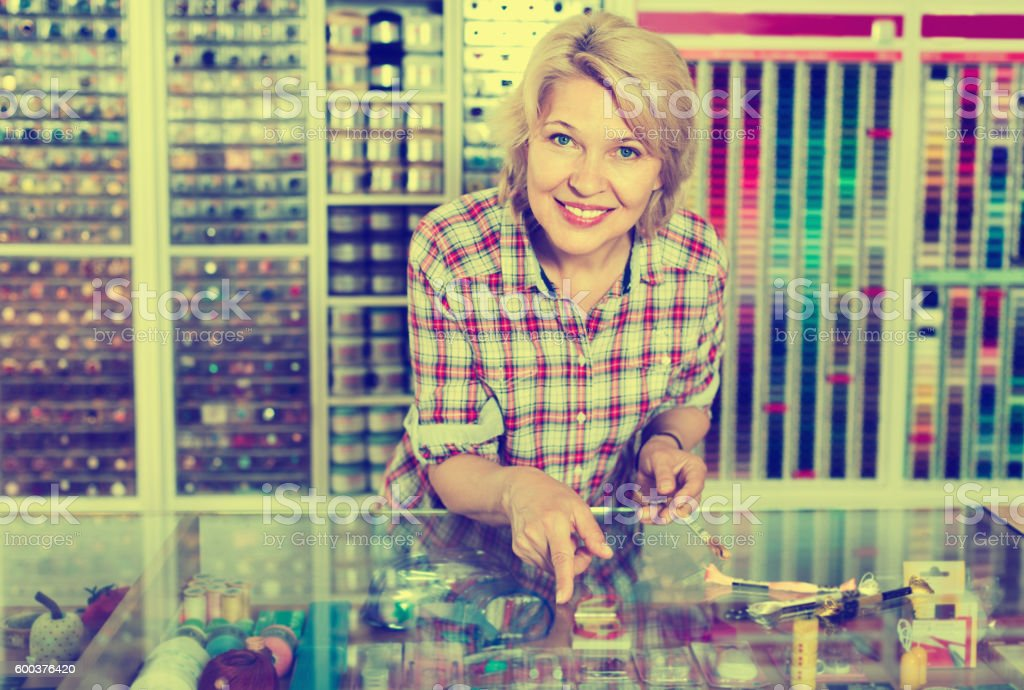 Mature  woman seller is ready to help at cash desk stock photo