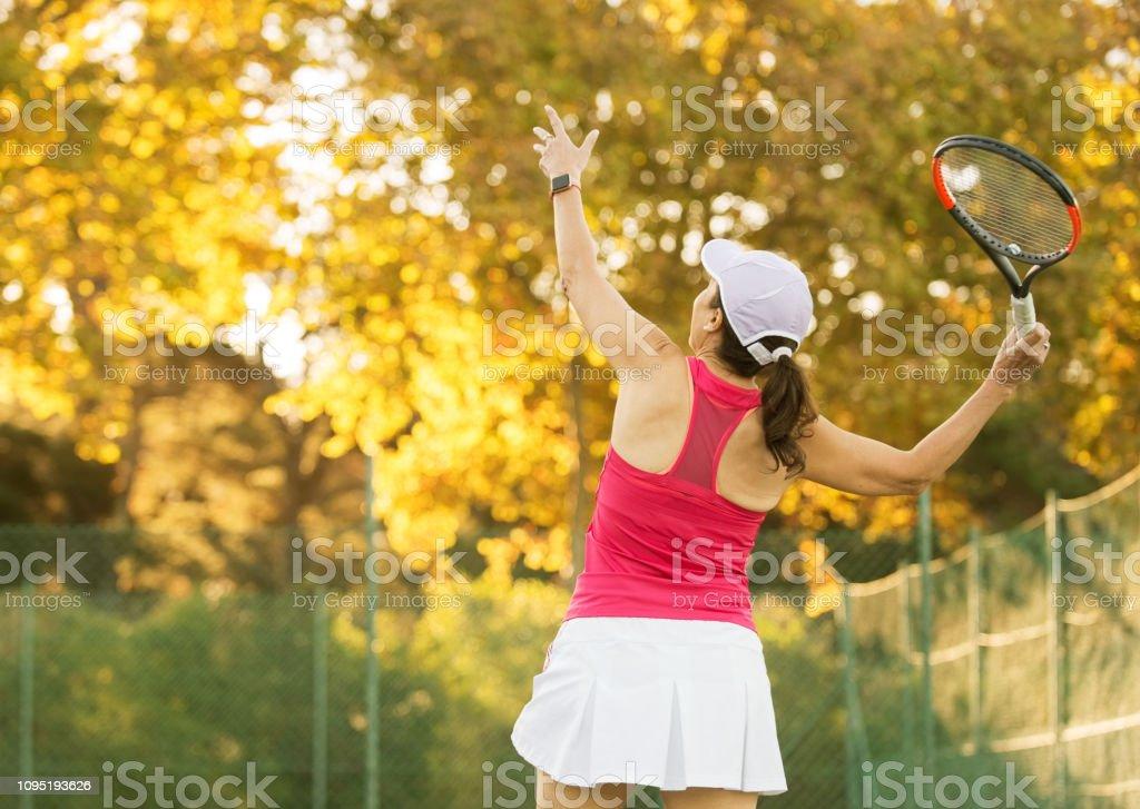 Shot of women serving ball during a tennis match on court.