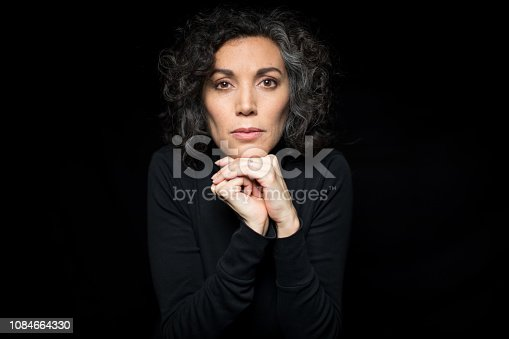 Portrait of mature woman shivering with cold with hand on chin. Mature caucasian female with short curly hair feeling cold on black background.