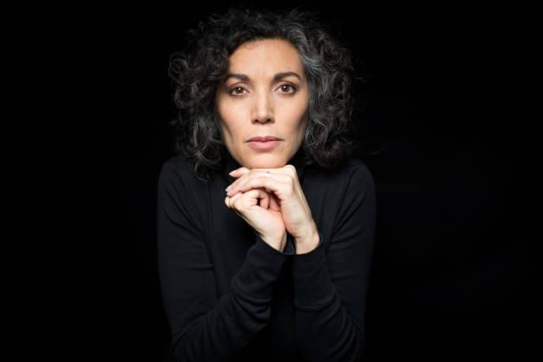 mature woman shivering with cold on black background - mano sul mento foto e immagini stock
